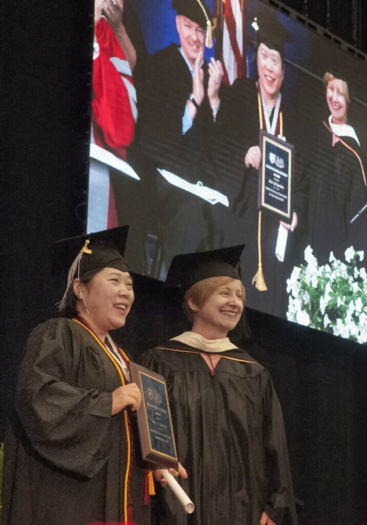 Lion Oyerbides, left, received the Kathleen Dexter Distinguished Student Award from Dean of Students Sheri Fraser on Saturday during the University of Maine at Augusta commencement at the Augusta Civic Center.