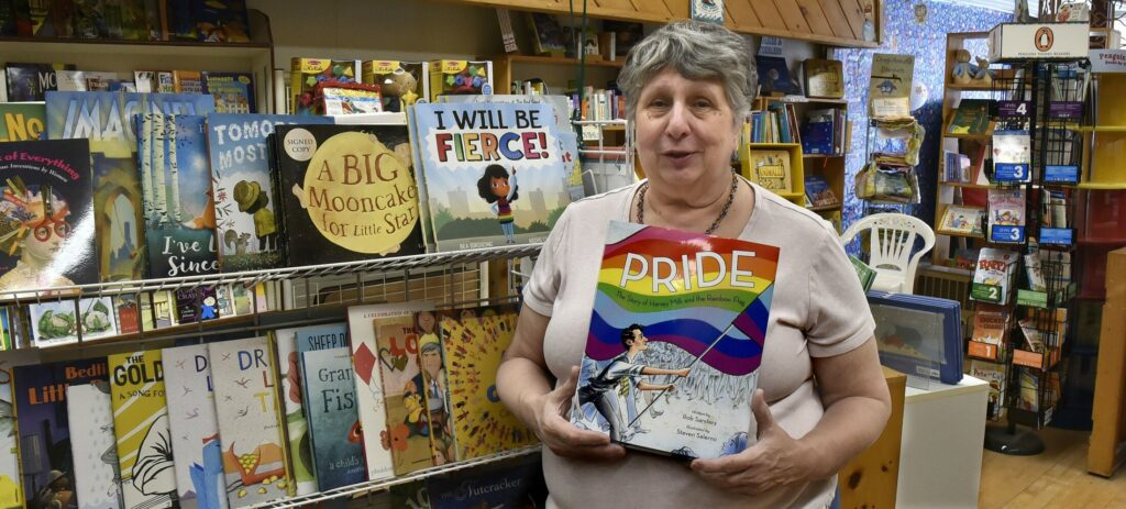 "Ellen Richmond, owner of the Children's Book Cellar in Waterville, holds a copy of the book ""Pride,"" based on the murder of gay San Francisco supervisor Harvey Milk, on May 13, 2019. The book store is one of the sponsors of a virtual reading by drag queen Valerie Honeywell Saturday."