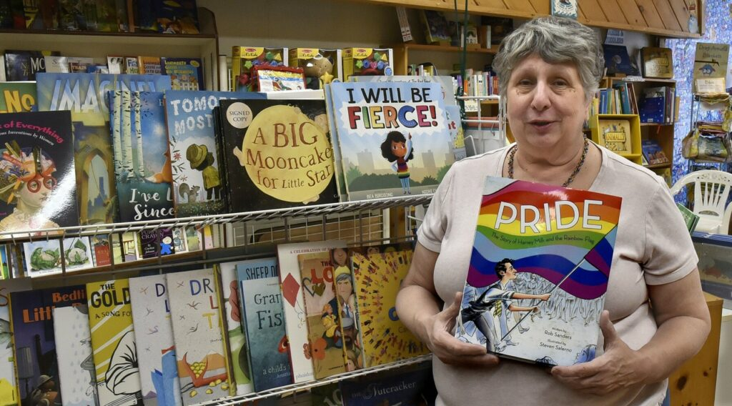 "Ellen Richmond, owner of the Children's Book Cellar in Waterville, holds a copy of the book ""Pride,"" based on the murder of gay San Francisco supervisor Harvey Milk, on May 13. Drag queen Valerie Honeywell will read at the bookstore on June 1 during Waterville's Pride celebration. ""I want to educate people about other lifestyles,"" Richmond said."