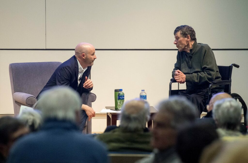 Travis Barrett, left, interviews George Smith, outdoorsman and writer, on Tuesday evening for Community Voices at the Ostrove Auditorium at Colby College in Waterville.