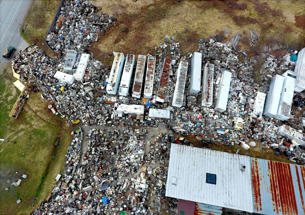 An aerial photograph of Robert Dale's property on May 1 defines the extent to which his stock has grown, squeezing out the driveway to U.S. Route 201 in Fairfield. Trailers not only contain material but support it on their roofs.