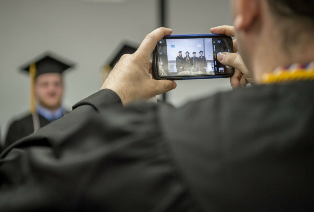 Kennebec Valley Community College graduates save the moment Saturday as they wait to march in to the Augusta Civic Center for their commencement ceremony.