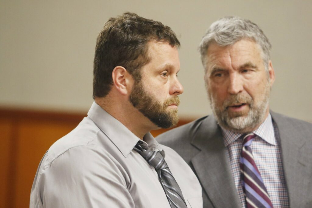 Shawn Purvis, left, stands in court with his attorney, Thomas Hallett, during his arraignment on the charge of workplace manslaughter in the death of a worker who fell from the roof of a house in December 2018.