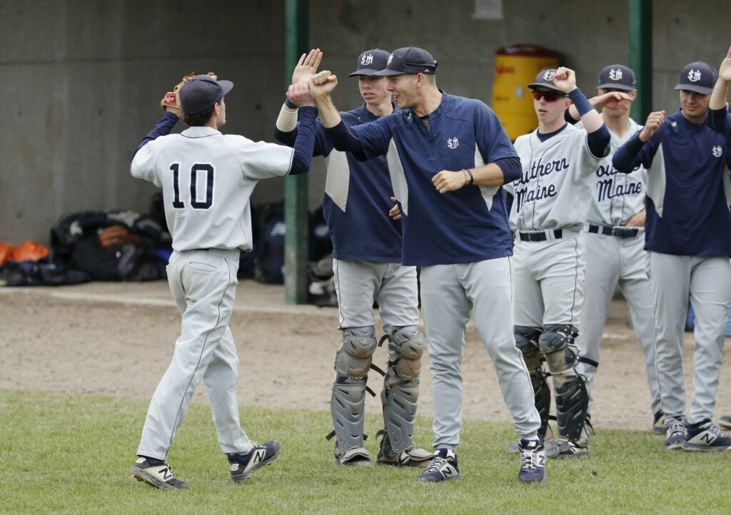 Ben Lambert is congratulated on his way to the dugout during the University of Southern Maine baseball team's 16-4 win over NEC in the NCAA Division III baseball tournament on Sunday in Gorham. The Huskies forced the winner-take-all game with the win.