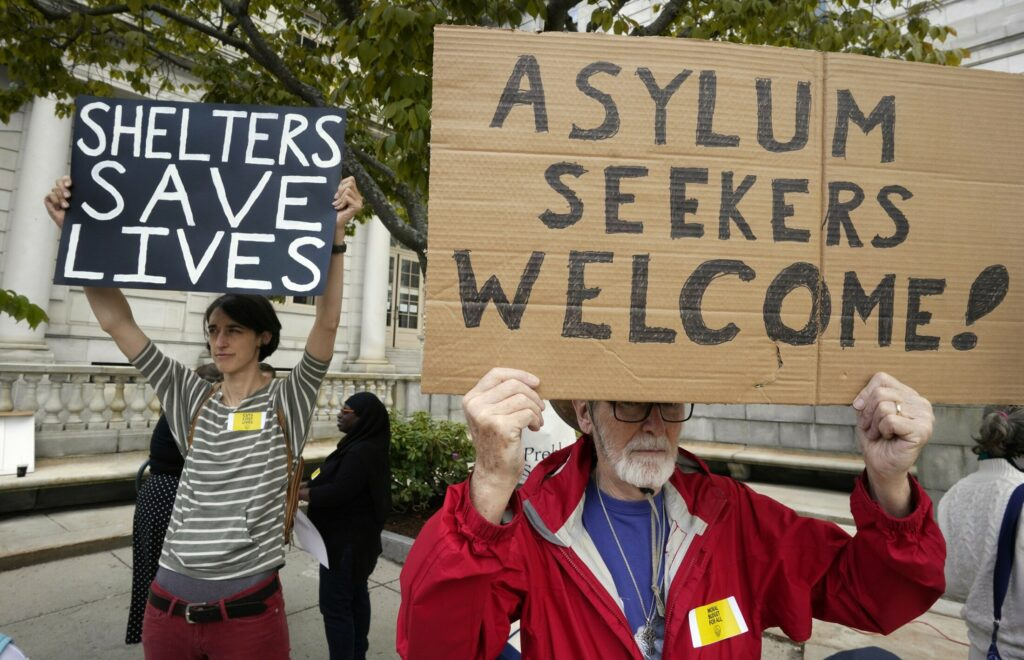 Peter Carleton, right, holds a sign in support of asylum seekers and Casey Ryder holds a sign in support of the city's shelter during a rally at Portland City Hall Monday. The two Portland residents were among over 100 people at a rally protesting potential cuts to the city budget.
