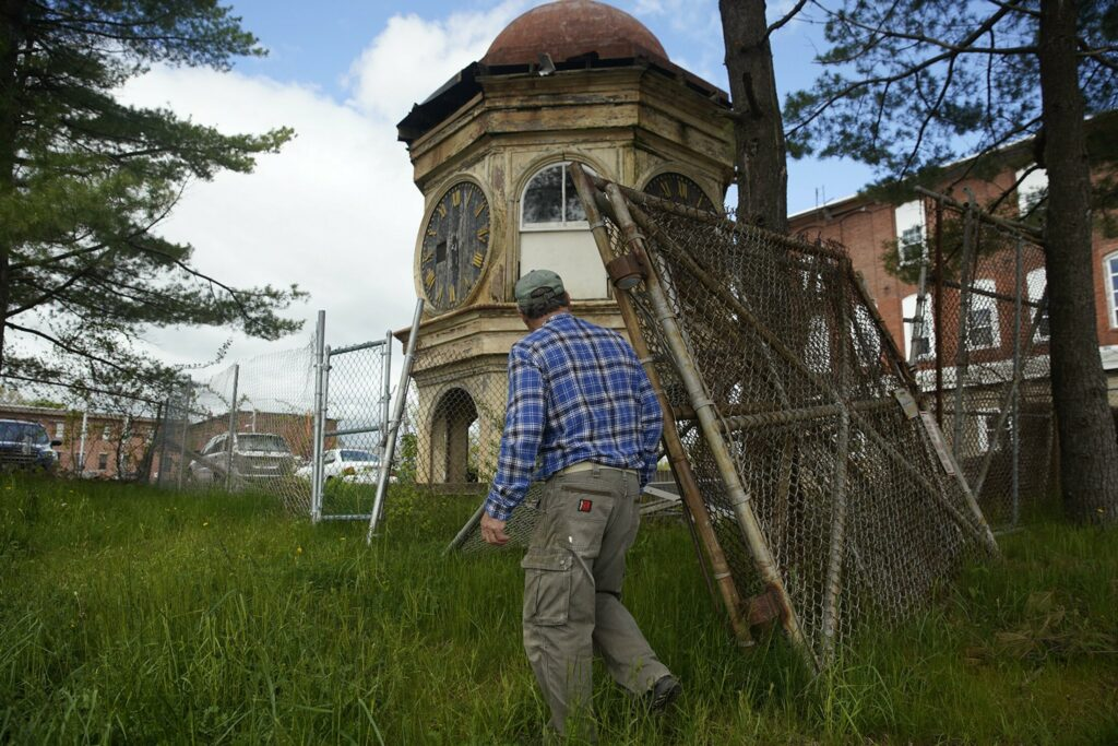 BIDDEFORD, ME - MAY 24: Dan LeBlond, a Biddeford resident and local historian, walks up to the clock tower that once sat atop the Lincoln Mill in Biddeford on Friday, May 24, 2019. LeBlond and a group of locals are trying to raise money to restore the clock tower, that was brought down form the mill in 2007, and put in in a public park. (Staff photo by Brianna Soukup/Staff Photographer)