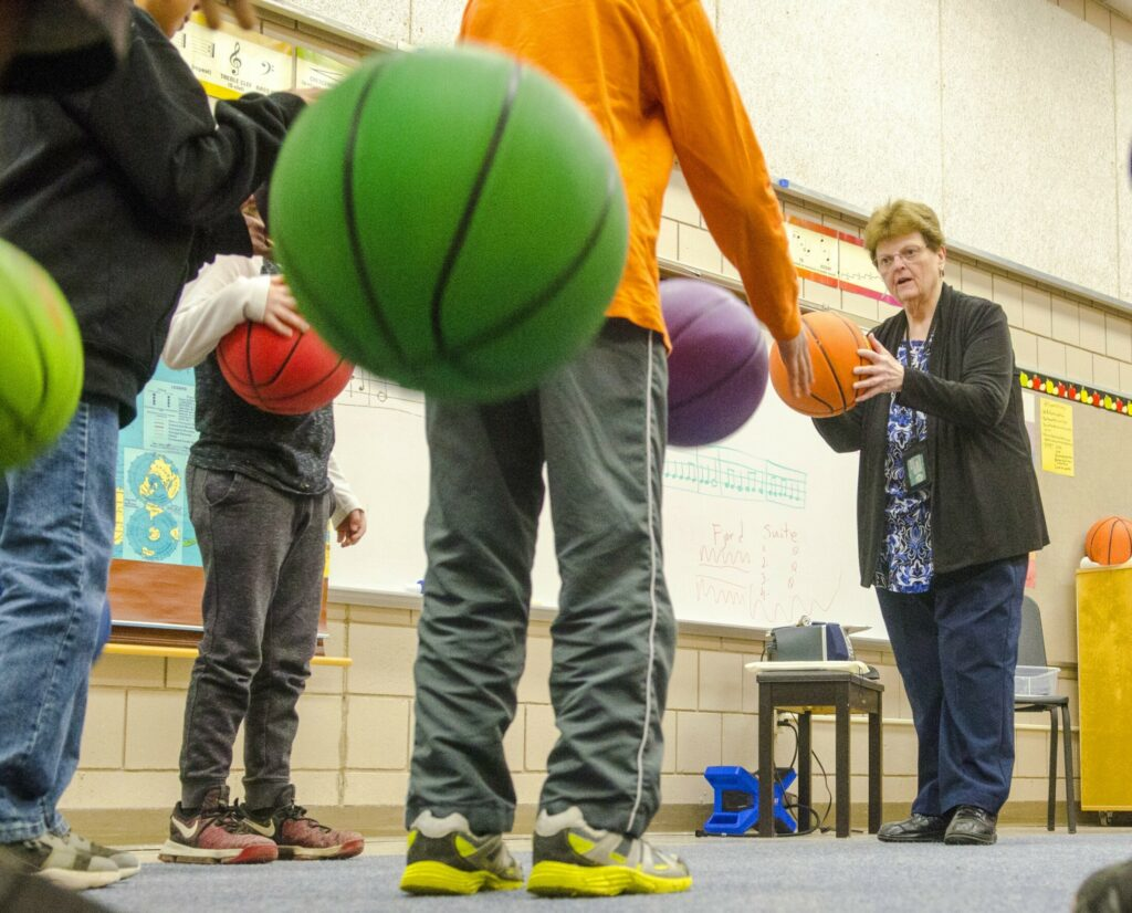 Music teacher Sharon Beaver instructs students Thursday at Farrington Elementary School in Augusta. They were bouncing the balls in tempo with recorded classic music.
