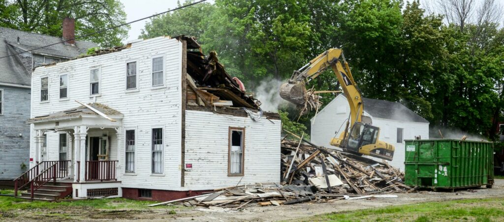 An excavator demolishes 18 Green St. in Augusta on Tuesday. The old house was across the street from Green Street United Methodist Church.