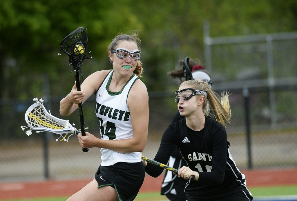 Waynflete's Emi Boedeker looks for an open teammate while being guarded by St. Dom's Isabella Webster in Wednesday's game. Waynflete won 11-2.