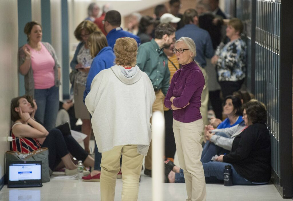 People gather in the hall Thursday during an executive session at a School Administrative District 49 school board meeting at Lawrence junior High School in Fairfield.