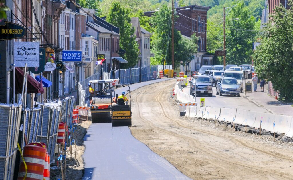A pair of rollers move along June 13, 2018, flattening the just-paved east side of Water Street in downtown Hallowell.