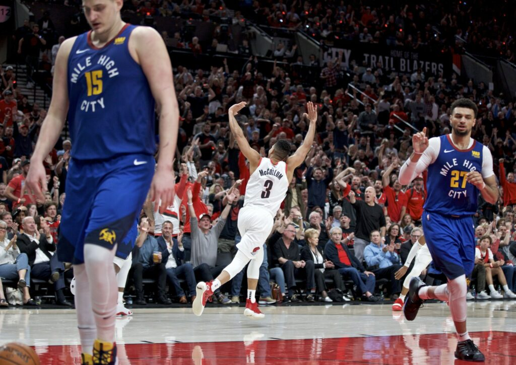 Trail Blazers guard CJ McCollum, center, reacts after making a 3-pointer during the  against the Denver Nuggets during Portland's 140-137 win in four overtimes in Game 3 of their Western Conference semifinal playoff series on Friday in Portland, Ore.