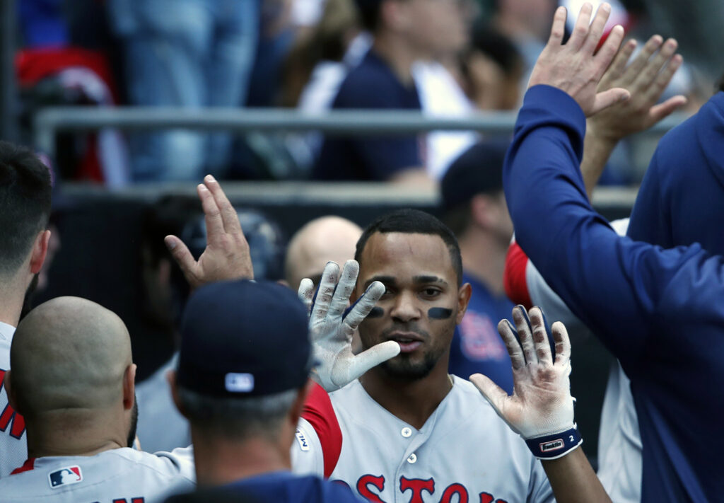 Boston's Xander Bogaerts celebrates with teammates in the dugout after hitting a grand slam in the eighth inning of the Red Sox' 9-2 win over the White Sox on Sunday in Chicago.
