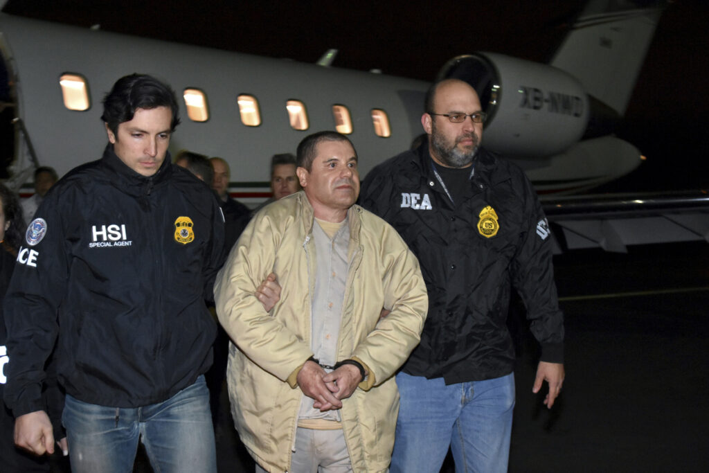 "In this Jan. 19, 2017 file photo provided U.S. law enforcement, authorities escort Joaquin ""El Chapo"" Guzman, center, from a plane to a waiting caravan of SUVs at Long Island MacArthur Airport, in Ronkonkoma, N.Y."
