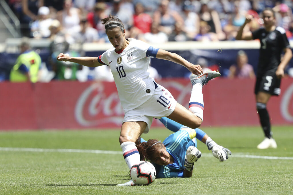 United States forward Carli Lloyd, center, dribbles past Mexico goalkeeper Cecilia Santiago to score a goal during the second half of an international friendly soccer match, Sunday, May 26, 2019, in Harrison, N.J. The U.S. won 3-0. (AP Photo/Steve Luciano)