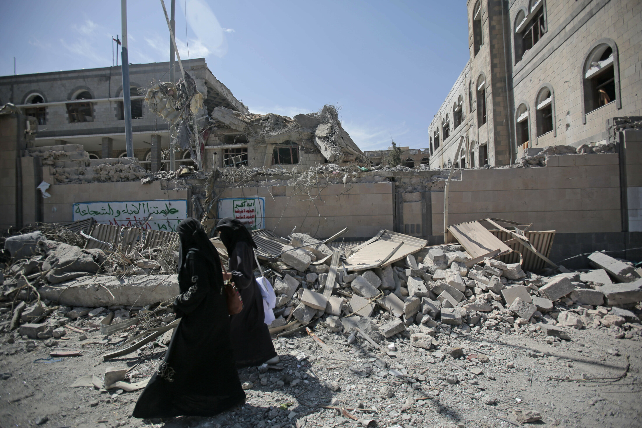 Yemenis walk past rubble after deadly airstrikes in and near the presidential compound, in Sanaa in 2018. Yemen's civil war started in 2014 when the Houthis overran the capital, Sanaa, and much of the country's north.