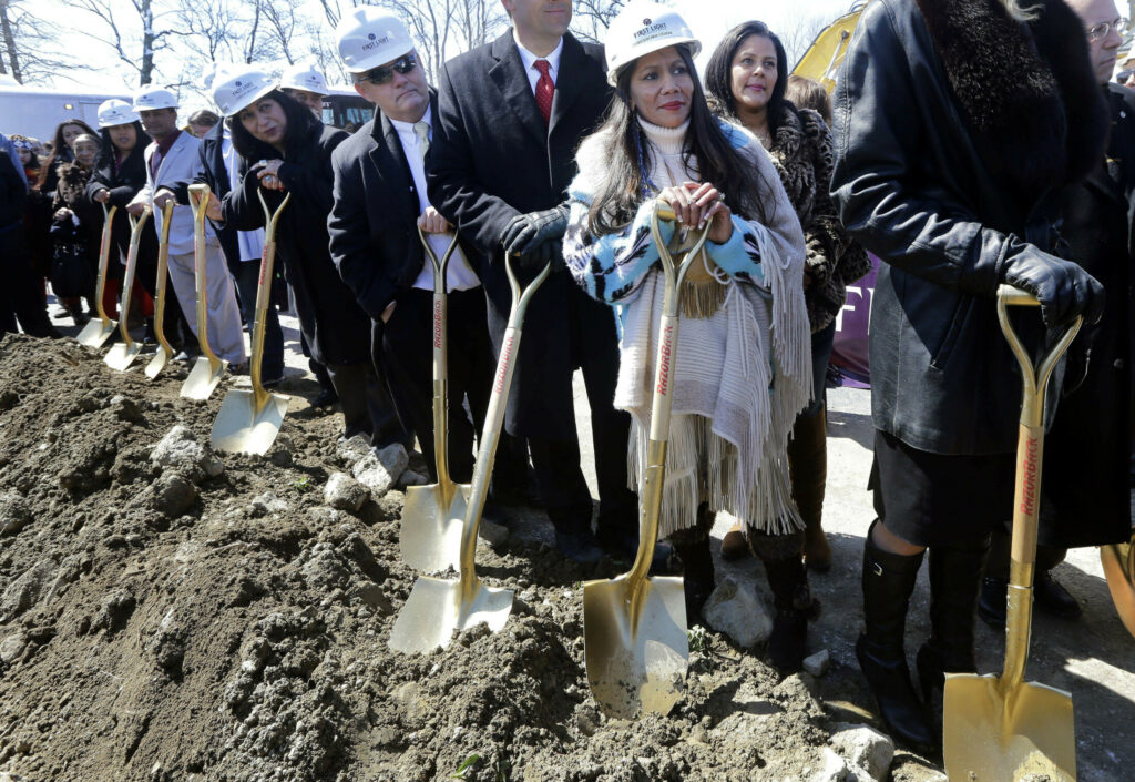 Mashpee Wampanoag Tribal Council member Winnie Johnson Graham, foreground, holds a shovel along with others during an official groundbreaking for a planned a resort casino in Taunton, Mass., on April 5, 2016. The project has yet to be built and has been caught up in political wrangling ever since.