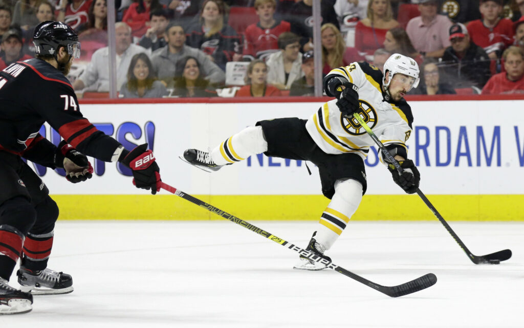 Boston Bruins' Brad Marchand (63) takes a shot on goal while Carolina Hurricanes' Jaccob Slavin (74) defends during the first period in Game 4 of the NHL hockey Stanley Cup Eastern Conference final series in Raleigh, N.C., Thursday, May 16, 2019. (AP Photo/Gerry Broome)