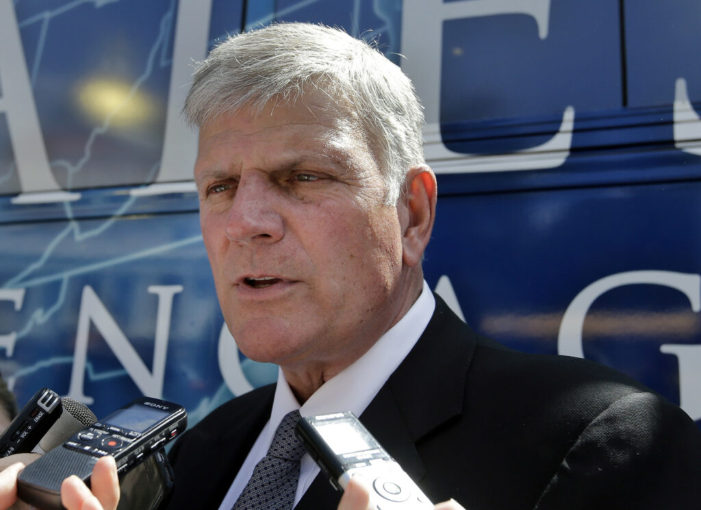 "Evangelist Franklin Graham speaks to media in front of his bus after a mass prayer rally on Boston Common in 2016 in Boston. Graham, the son of famed evangelist Billy Graham, is holding a 50-state ""Decision America"" tour to urge evangelicals to vote."