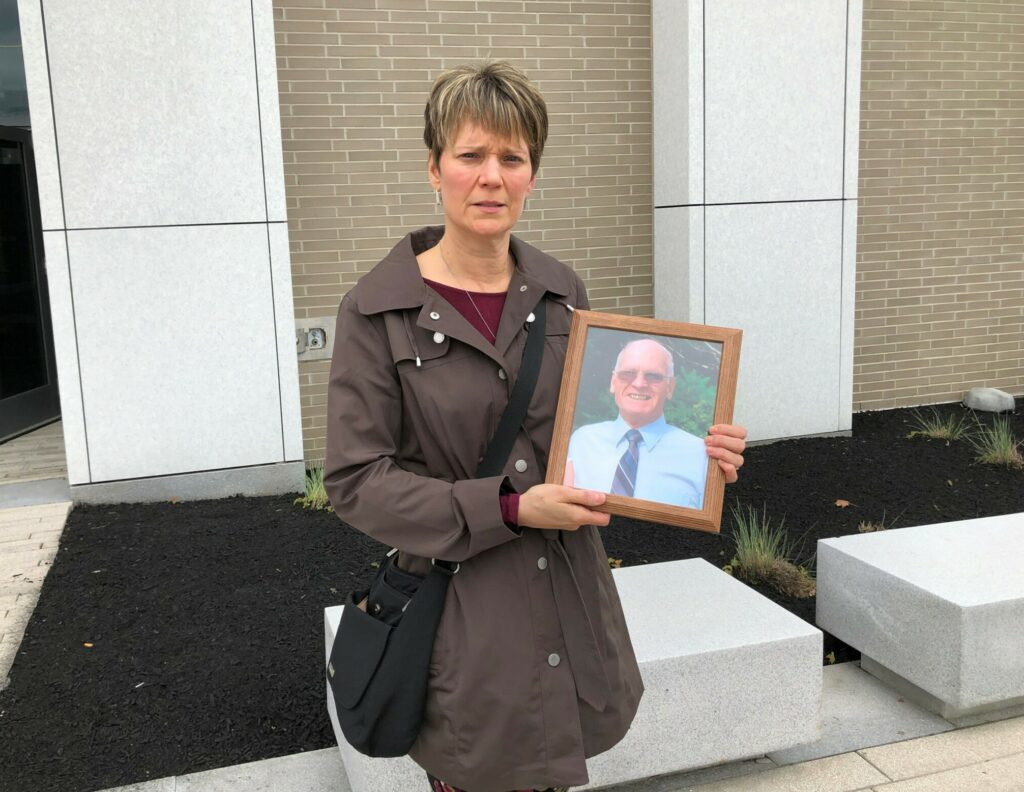 Caryn Murphy, daughter of the late Emile Morin, holds a photo of him that the family brought to court on Wednesday.