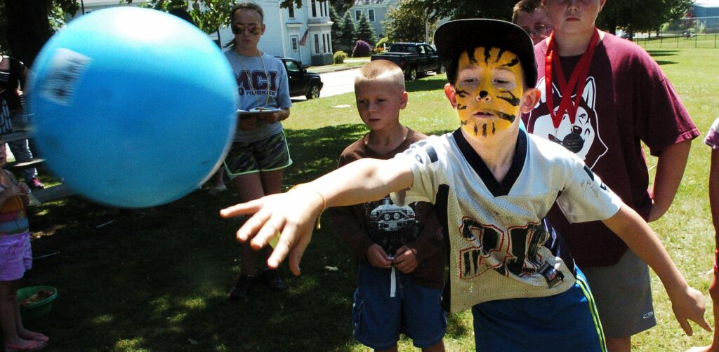 After getting his face painted as a tiger Joshua Stineford  tosses a ball into a bucket during Egg-Olympics activities of the Central Maine Egg Festival in Pittsfield on July 13, 2016.