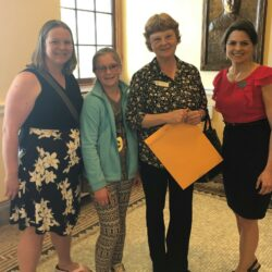 Jess McGreevy and Charlotte McGreevy stand with Oxford County Teacher of the Year Linda Andrews, who received a legislative sentiment from Sen. Lisa Keim at the State House on May 9.