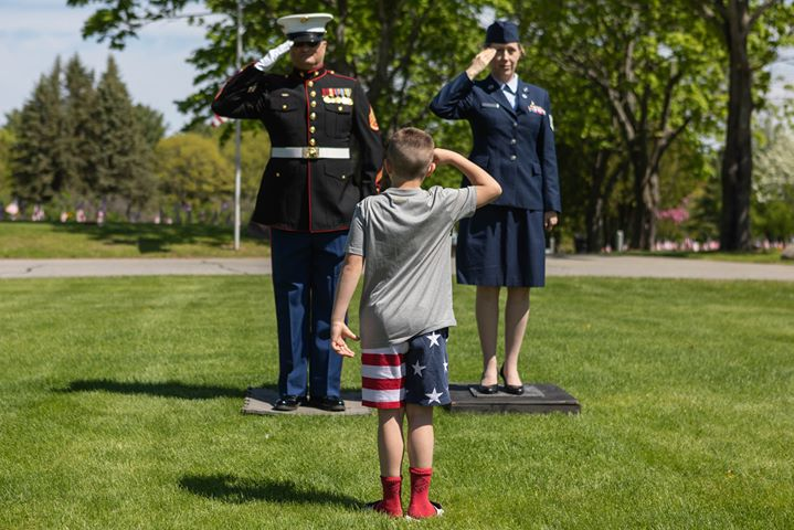 US Marine Ricky Harrington, of Oakland, left, and US Air Force Lorie Roy, of Waterville, right, stand at attention at the Maine Veterans Memorial Cemetery on this memorial day to honor their fallen soldiers. Harrington has been showing his respect on Memorial Day for the past eight years by standing at attention from 10 a.m. to 1 p.m. He brings a display of war memorabilia representing the Civil War to the present, some of which include boots that were worn on several different continents, dog tags from every branch of the service, moss from Parris Island and a WWI combat helmet from the founders of the Oakland American Legion. While he was standing there for a short time, a 7-year-old Kemden Hafford faced them to salute.