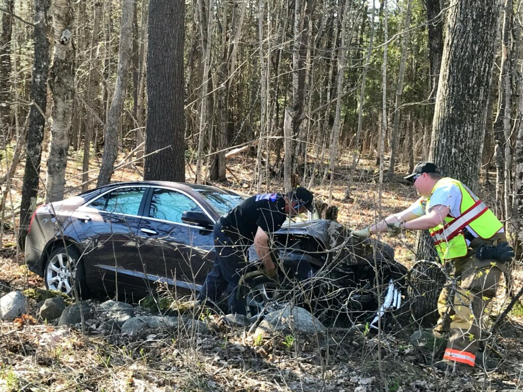 Fire and rescue workers work to remove a car that crashed into a tree Monday on U.S. Route 2 in Pittsfield. The driver of the vehicle was pronounced dead at the scene.