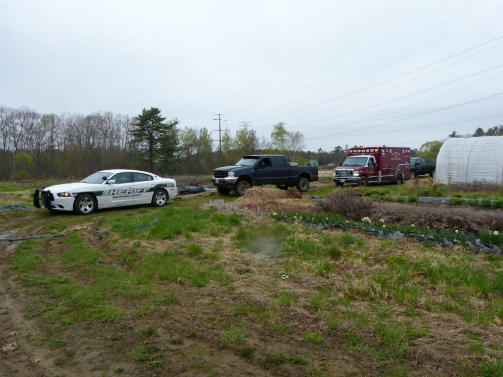 Emergency vehicles parked at East of Eden Flower Farm in Bowdoinham, near where police recovered a body from Merrymeeting Bay Friday morning.