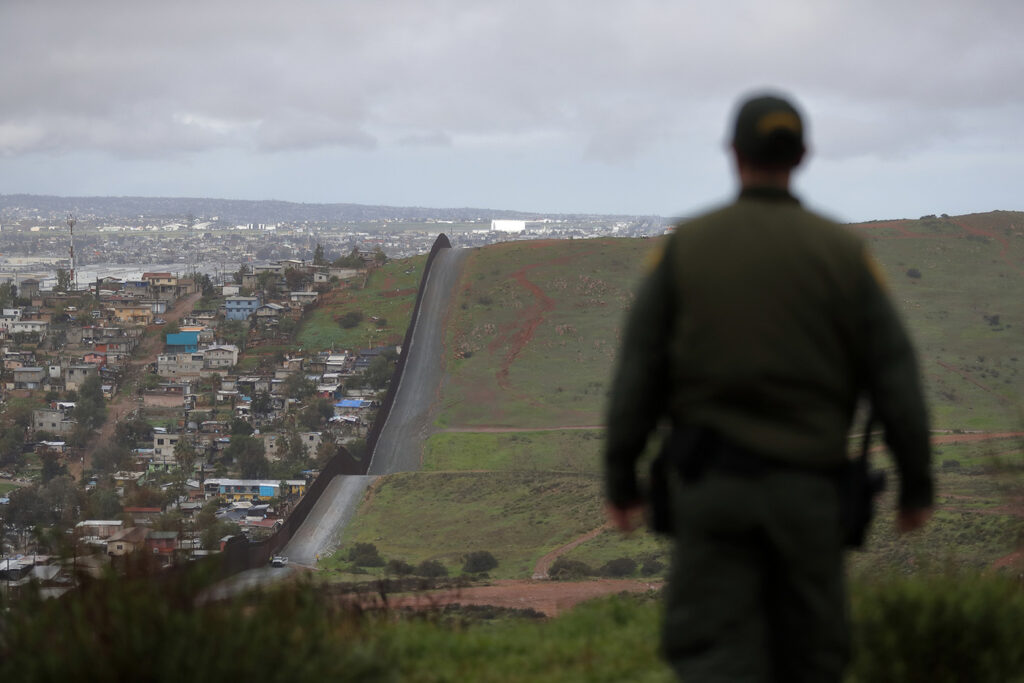 A U.S. border patrol officer overlooks the wall that separates the cities of Tijuana, Mexico, and San Diego.