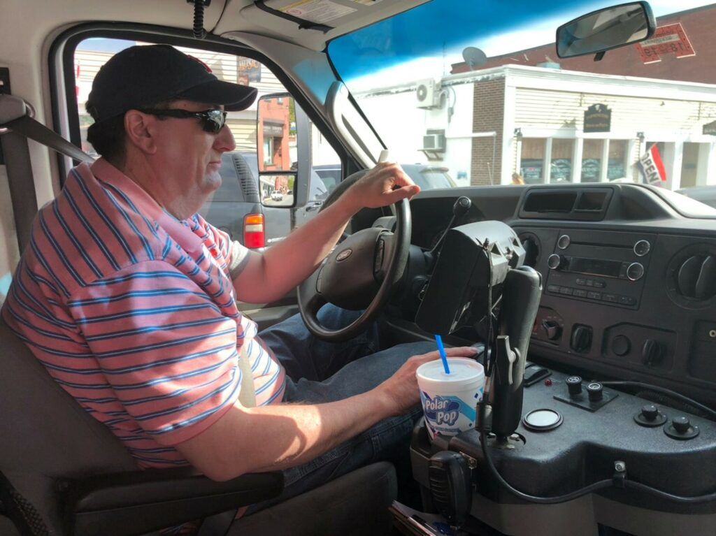 Walt Webber drives the Western Maine Transportation Services bus Thursday afternoon from Wilton to Farmington. Webber has been driving the bus, which offers low-fare service to Franklin County residents, for about five years.