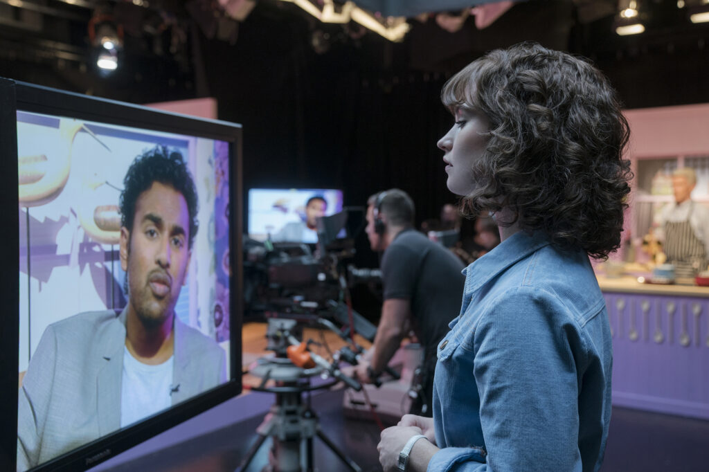 """Himesh Patel, left on TV screen, and Lily James star in """"Yesterday."""" MUST CREDIT: Jonathan Prime, Universal Pictures"""