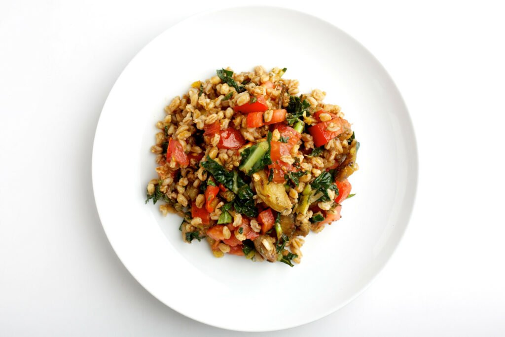 Eating ancient grains such as farro, shown in a salad with tomatoes, grilled vegetables and kale, can help support biodiversity. MUST CREDIT: Photo by Deb Lindsey for The Washington Post.