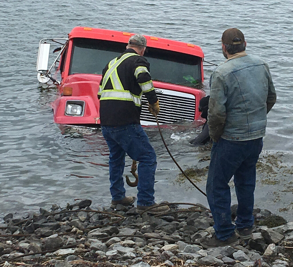 The wrecker owned and operated by Harold Gray of Bowdoin is submerged off of Hills Way in Harpswell after the ground gave way underneath it as it was delivering a dock on Wednesday.