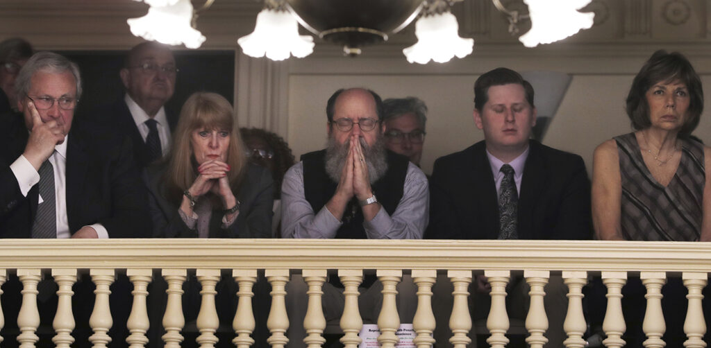 Rob Spencer, center, of Concord, N.H. pauses in prayer as legislators debate prior to a death penalty vote at the State House in Concord, N.H. on Thursday.