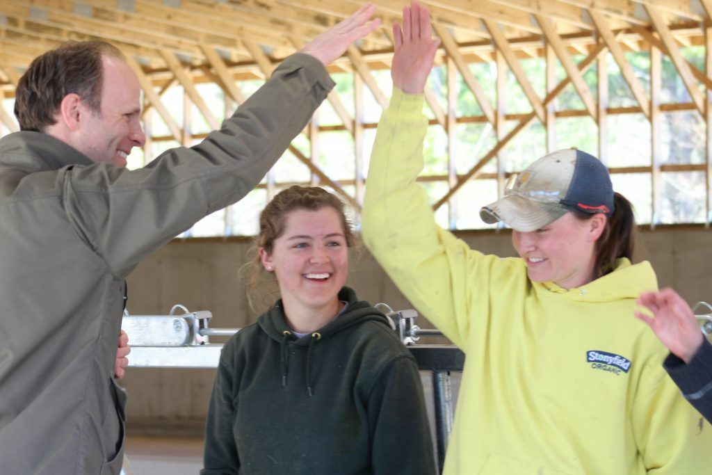 David Herring, executive director of the Wolfe's Neck Center for Agriculture and the Environment, high-fives dairy farmer apprentices Corinne Carey, left, and Tierney Lawlor at the grand opening of the center's organic dairy facility Thursday. Herring directed everyone to celebrate the opening with high fives in lieu of a ribbon cutting.