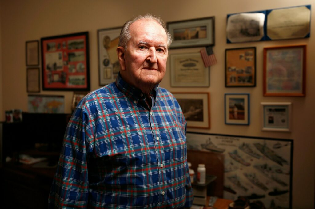 Bob Ryan, photographed in front of a wall covered with his war memorabilia, was a member of the U.S. Navy's Seabees during World War II and arrived on Omaha Beach just hours after U.S. forces pushed the Germans inland on D-Day.