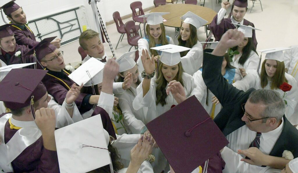 Monmouth Academy Principal Rick Amero leads seniors in a group cheer before marching into graduation ceremonies June 9, 2019. For this year's ceremony the students, and Amero, won't be able to be that close, but they will all graduate together in a socially distanced ceremony.