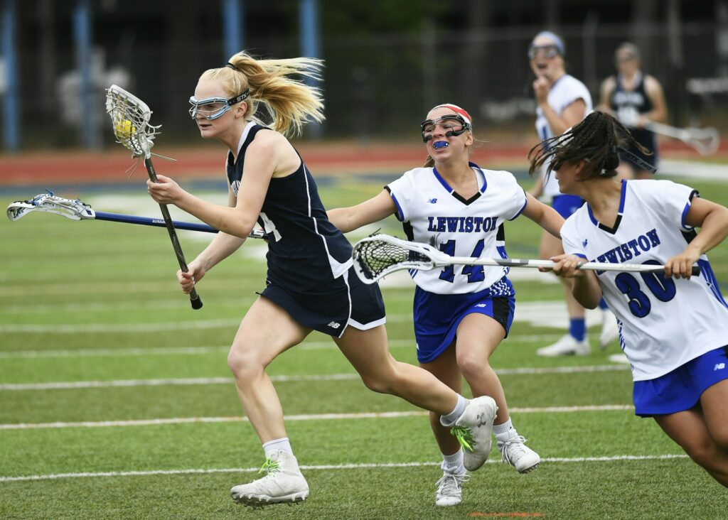 Portland's Annika Moore runs with the ball as she tries to elude Lewiston's Melina Masseli and Paige Pomerleau.
