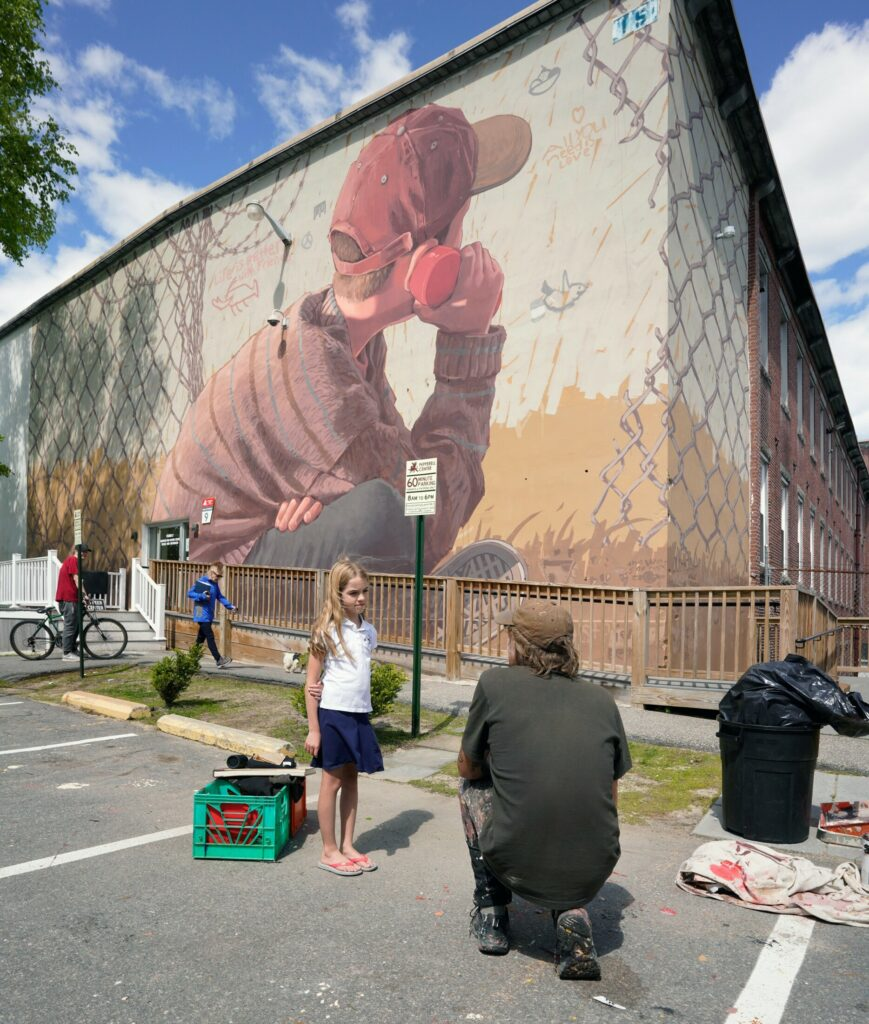 Artist Pat Perry talks with Rhys Cote on Tuesday about the mural he painted on the side of a building in Biddeford. The mural is paired with a similar mural that Perry painted in Iraq. Rhys is a fourth-grade student at St. James School in Biddeford and came by with her mother to see the mural.