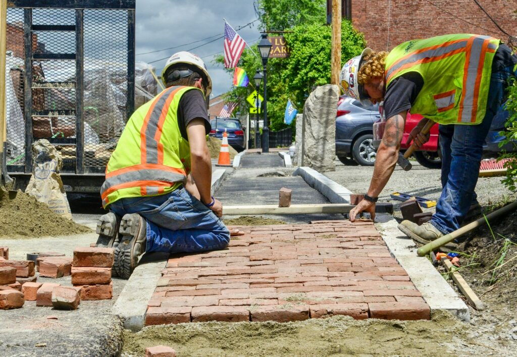 Sargent Corp. workers Ryan Modery, left, and Dustin Dugan build a narrower sidewalk Thursday in front of the Lucky Garden restaurant's parking lot along Water Street in Hallowell.