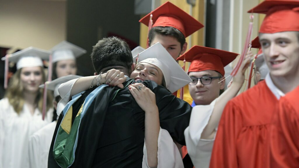 Cony High School teacher Jason Morgans hugs every graduate he can Sunday before marching into graduation ceremonies in Augusta.