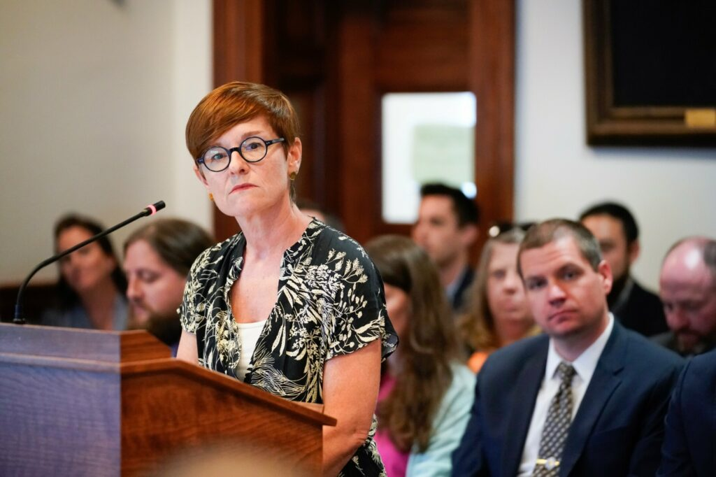 Patricia Rosi, CEO of Wellness Connection, listens to a question from a member of the Veterans and Legal Affairs Committee during a hearing Monday on rules for marijuana businesses. A lobbyist for Wellness Connection said the company will consider suing the state if it can't participate in the recreational market because of the proposed regulations.