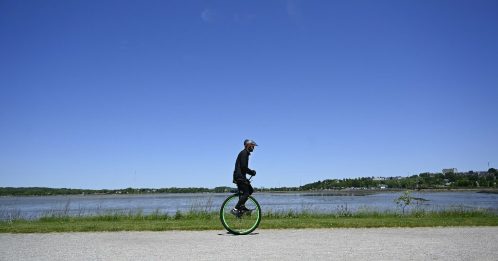 Hugh Sharp, the first person to complete the 180-mile Trek Across Maine on a unicycle, rides on Portland's Back Cove Trail on Wednesday.