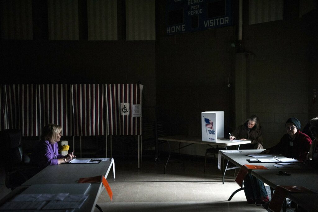 Volunteers and voters work in the dark to cast ballots after a power outage at a voting station at the Fairfield Community Building in Fairfield on Tuesday.  The SAD 49 school district budget was on the ballot.