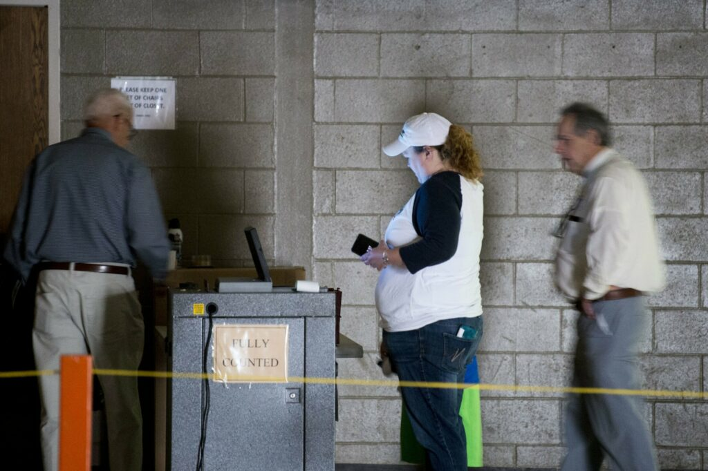 Volunteers and voters work in the dark to cast ballots Tuesday after a power outage at a voting station at the Fairfield Community Building. The School Administrative District 49 school district budget was on the ballot.