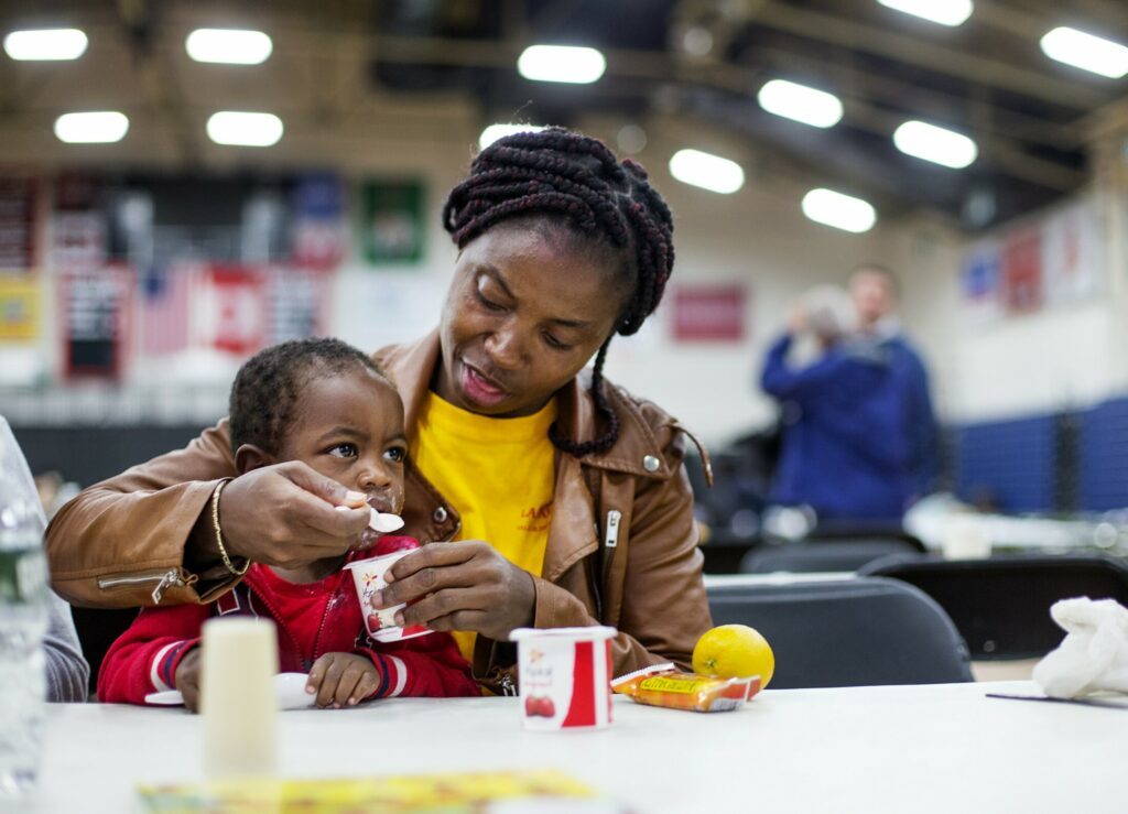 An asylum seeker from Cameroon, who did not want to give her name, feeds her son Thursday at the emergency shelter the city has set up for asylum seekers at the Portland Expo.