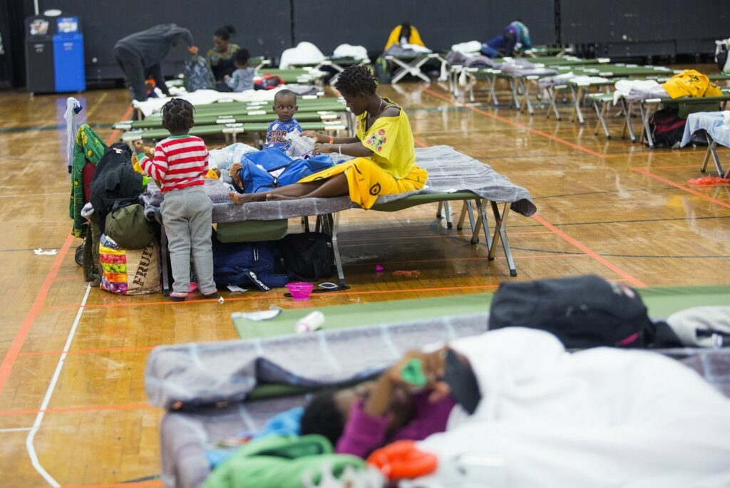 Families rest on cots in June at the Portland Expo, which the city opened as a temporary emergency shelter for asylum seekers. In about two weeks, The Expo will revert to its role as a sports arena.