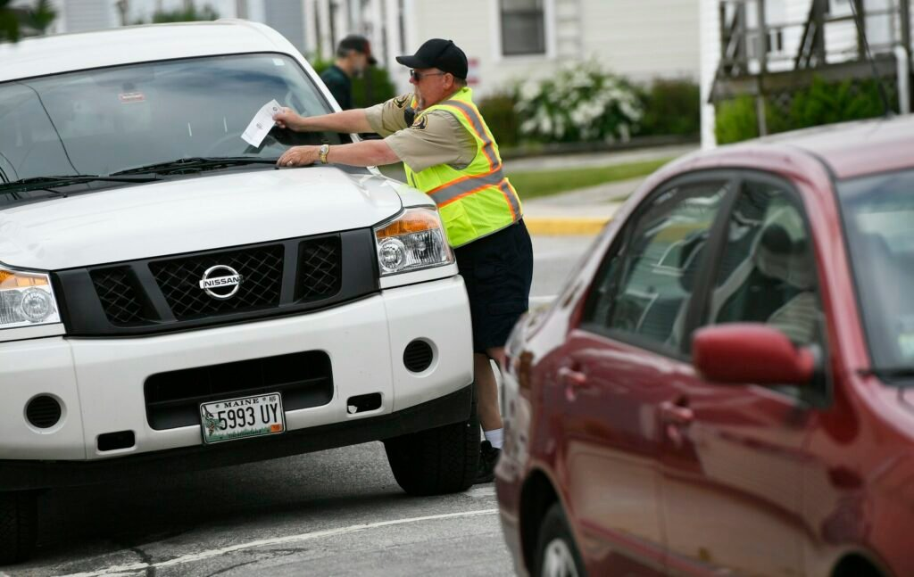 A parking enforcement officer places a ticket on a vehicle parked on Washington Street in downtown Biddeford in June.