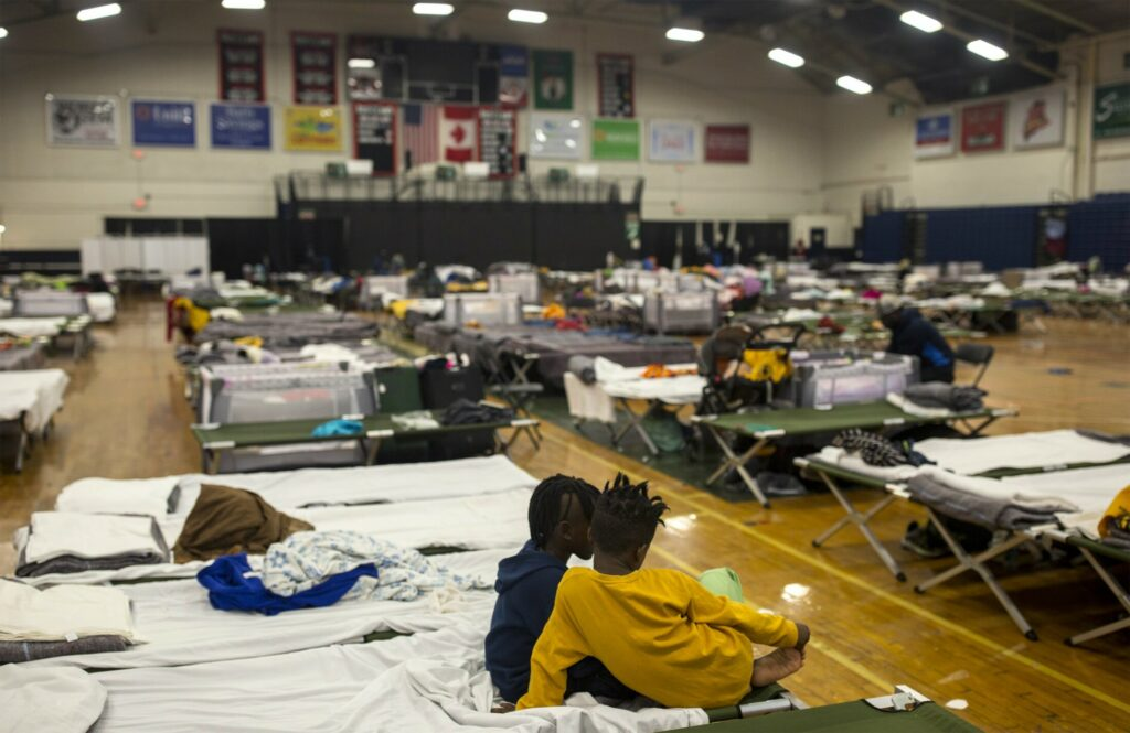 Two children sit on one of the cots set up for asylum seekers in the emergency shelter at the Portland Expo on JUne 19.